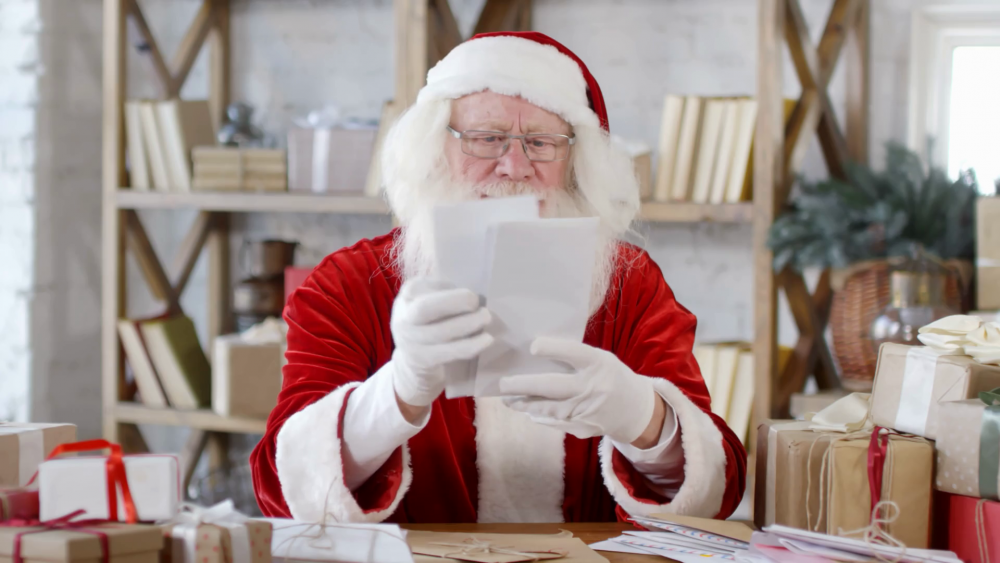 videoblocks-cheerful-santa-claus-checking-christmas-mail-while-sitting-at-desk-in-his-office-with-gift-boxes-and-envelopes-on-it_r9qhxxmur_thumbnail-1080_01.png